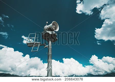 Wide-angle shooting of modern metal snow emitter tower set for winter sports with metallic area for operator next to ladder dramatic cloudscape in background and teal sky Sochi Estosadok district