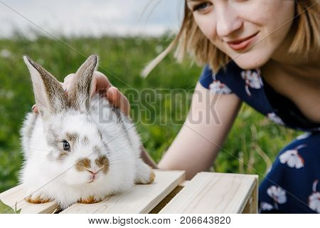 Young girl with a little rabbit. A woman holds a rabbit in her arms. Pets on a green field with a girl. Fluffy home-loving ones in the arms of a happy owner.