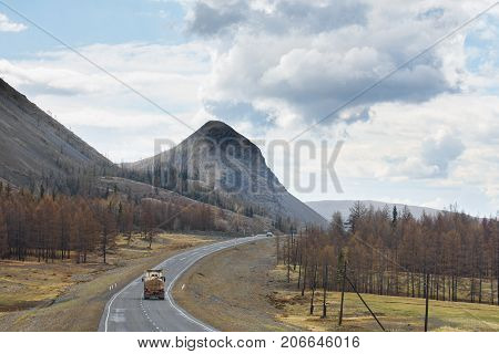 car driving on road at root of mountains and fluffy clouds on sky