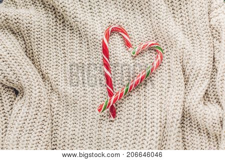 Christmas Candy In Heart Shape And Cozy Sweater On Rustic Background Top View, Space For Text. Xmas