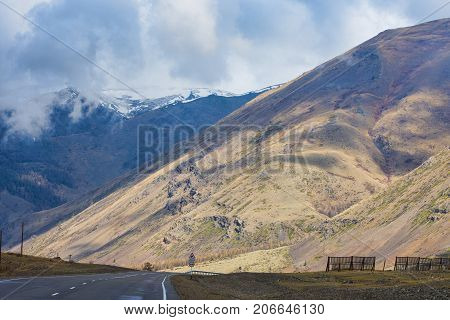 plain with highway at root of mountains and fluffy clouds on sky
