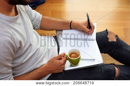 Left Handed Man Writing, Sitting On The Floor.
