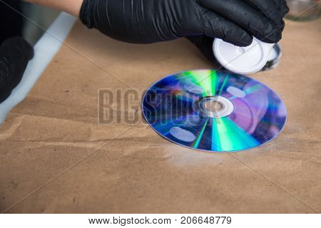 forensic hand in glove brushing for search latent fingerprints evidence by white powder on compact disc with copy space