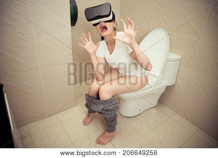 Attractive Shocked Girl Sitting On Bathroom Toilet