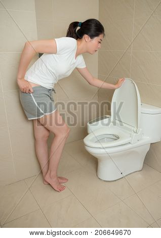 Lovely Woman Opening Toilet Lid And Holding Pant
