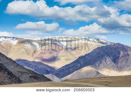 panoramic view of plain with road at root of mountains and fluffy clouds on sky