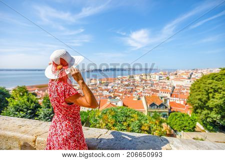 Woman admires Lisbon skyline from Sao Jorge Castle in Alfama. 25 April Bridge, Tagus River and Baixa District on blurred background.Tourism and travel in Portugal.Lisbon Castle is a popular attraction