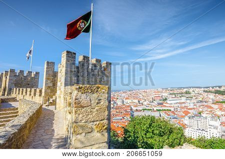 Portugal flag waving on ancient fortress wall of Sao Jorge Castle, at Moorish castle on highest hill in Alfama. Lisbon aerial cityscape on background. Lisbon Castle is a popular tourist attraction.