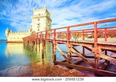 The iconic and spectacular Belem Tower and wooden jetty reflecting on Tagus River with low tides. Torre de Belem is Unesco Heritage and famous city landmark in Lisbon, Belem District, Portugal.