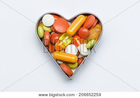 heart-shaped cordatly bunch of colored pills isolated
