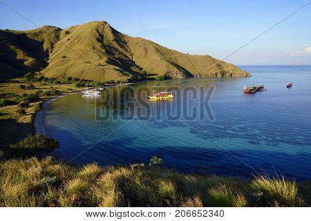 Padar Island with scenic high view of boats and beautiful white sandy beaches surrounded by a wide ocean and part of komodo national park in Flores Indonesia