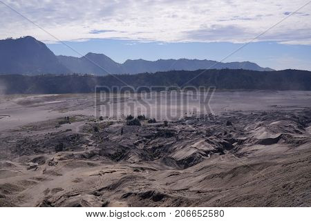 Panoramic view from the top of the stairs heading towards the dusty valley behind hindu temple at the foot of mount Batok at the Tengger Semeru National Park in East Java Indonesia.