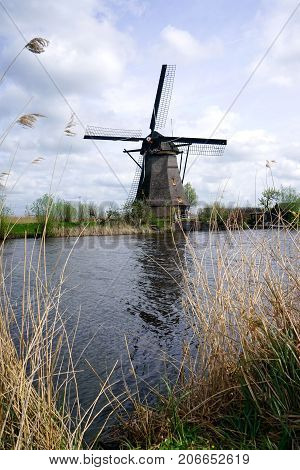 Dutch windmill in the afternoon build and standing next to polder water in kinderdijk south holland used to drain water out by using wind power and keep land dry.