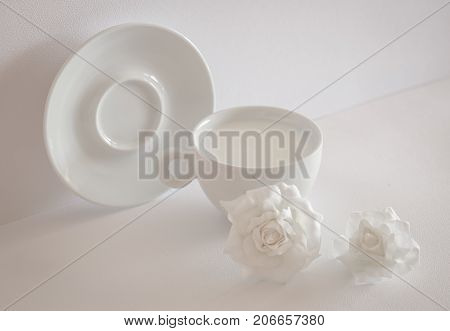 Stillife in high key. White cap with milk plate and flowers