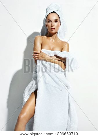 Beautiful woman in white bathrobe after spa. Photo of well-groomed woman on white background. Wellness and Spa concept