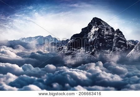 A majestic, snow capped rugged mountain peak towers above the cloud tops.