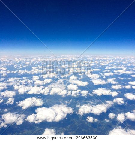 From above the clouds, this image shows beautiful colours and patchy clouds which allow you to see through to the ground below.