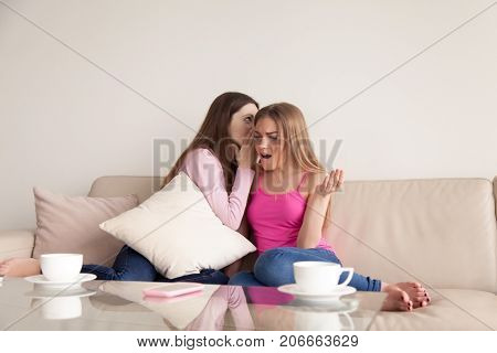 Young girl whispers personal secret into her friends ear. Girlfriend listens with surprised expression on face. Best friends gossip about people they know, telling latest rumors, share private news.