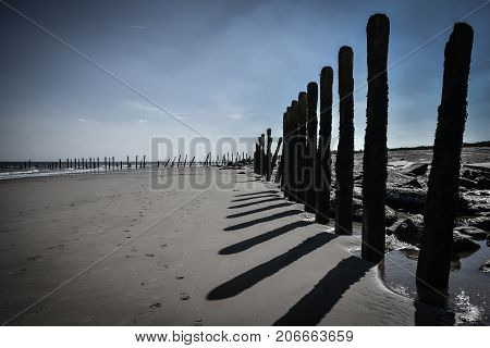Black and white seascape with wooden pillars as leading lines