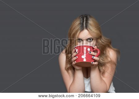 Studio shot of long haired young woman drinking from red spotted mug. All on the gray background.