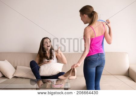 Girl screaming with excitement and showing thumbs up towards her girlfriend. Overly excited young woman approves her friends new outfit and shoes. Successful shopping, getting ready for date concept.