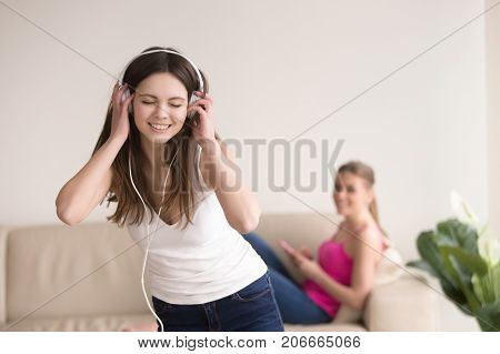 Young happy smiling girl in stylish white headphones listening to favorite music in living room at home. Her girlfriend or sister relaxing on sofa with smartphone in hand. Girls having fun concept.