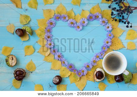 Cup of coffee and symbol of heart with autumn flowers on old wooden blue background. symbol of heart with autumn flowers. old wooden blue background.Concept autumn.