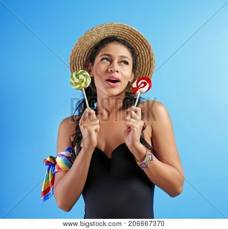 Beautiful young woman in swimming suit and with lollypops on color background
