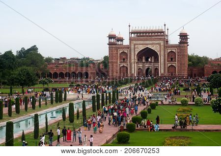 Agra, India - 12 Aug 2017: The huge arched sandstone entry gate for the Taj Mahal. This famous monument attracts huge crowds clearly seen here.