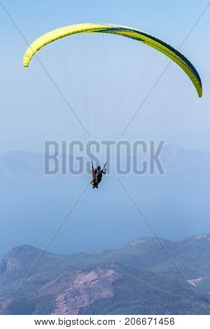 Skydiver landing with a awesome mountains background. Oludeniz