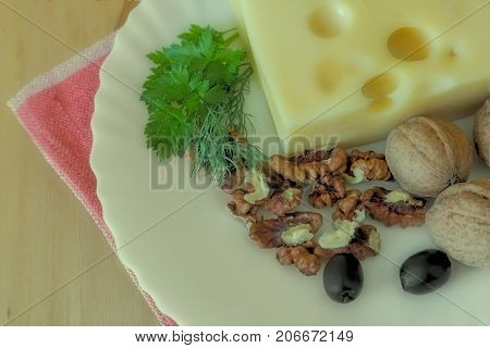On the table on a white plate to get the cheese, walnuts and olives. The effect of the Polaroid.