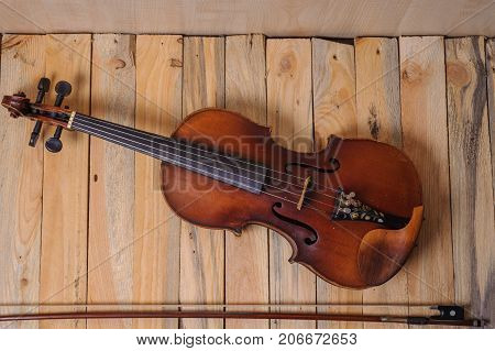 one violin image .old brown stringed wooden instrument isolated on the wood background and bow