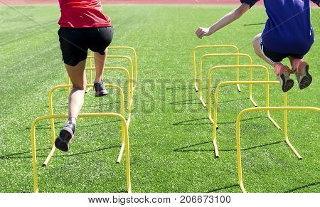 Two athletes perform coordination and strength drills by jumping over mini hurdles on a green turf field at practice.