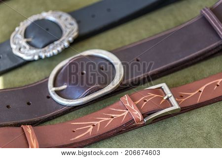 Belts and buckles for clothes on the table. Close up