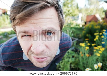 Closeup character portrait of a man with blue eyes looking at the camera with questioning and suspicious facial expression in summer outdoor