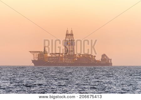 WALVIS BAY NAMIBIA - JULY 2 2017: An oil drilling ship anchored after sunset in the Atlantic Ocean at Longbeach in the Namib Desert of Namibia