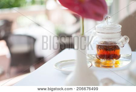 Glass teapot infuser on table for teatime flower white beautiful