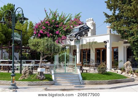 FALIRAKI, GREECE - AUGUST 2017: Small street restaurant decorated with mini cooper car suspended on a roof in Faliraki town on Rhodes island, Greece
