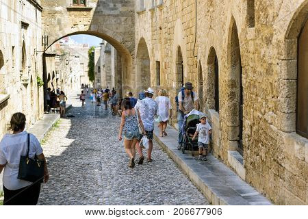 RHODES, GREECE - AUGUST 2017: Tourists at narrow street of Rhodes old town on Rhodes island.