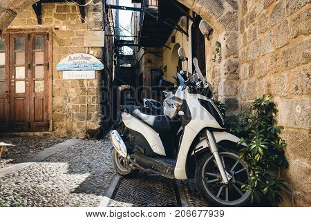 RHODES, GREECE - AUGUST 2017: Motorbike scooters are parked near the wall at narrow street of Rhodes town on Rhodes island, Greece