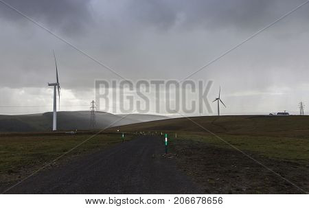 Wind turbines with an access road in a storm with lashing rain and heavy clouds.
