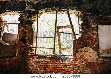Inside ruined abandoned house building after disaster, war, earthquake, Hurricane or other natural cataclysm. Big broken window with rubbish
