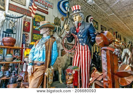 New York September 25 2017: Colorful wooden statues of Uncle Sam and a cowgirl dressed in blue shirt stand among a variety of other items in a Wild West themed store in Manhattan.