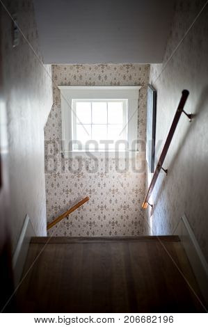 fleur de lis wall paper in spooky haunted house stairs