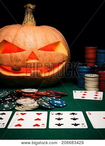The Concept Of Halloween. Evil Scary Pumpkin Plays Poker. Jack Lantern Among Poker Chips And Cards