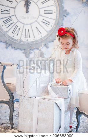 girl in a white elegant dress untying ribbon on Christmas gift wrapped in light gift paper. Girl on the background of clock showing midnight. Background for New Year's greeting card