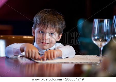 Cute toddler boy in a fancy indoor restaurant