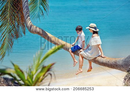 Mother and little son at tropical beach sitting on palm tree during summer vacation, Thailand