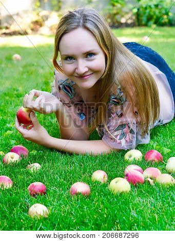 Young woman lying on grass holding an apple