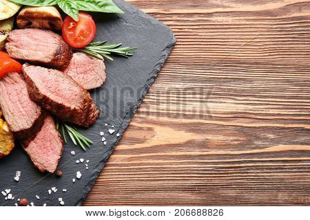 Tasty juicy meat with vegetables on slate plate